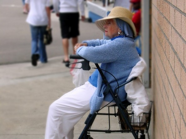old woman sitting on wheeled walker
