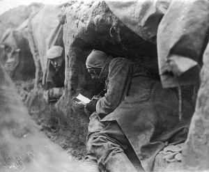 soldier in a trench writing letter