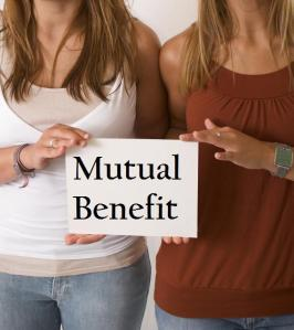 women holding sign 'mutual benefit'